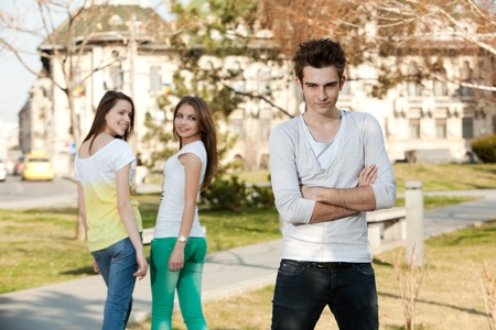 cool boy: two young women looking at a young man, in the park Stock Photo