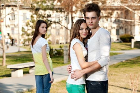outdoor photo of a young woman jealous on a happy couple photo