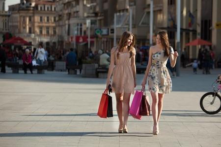 chicas de compras: dos mujeres j�venes con bolsas de compras caminando en la ciudad