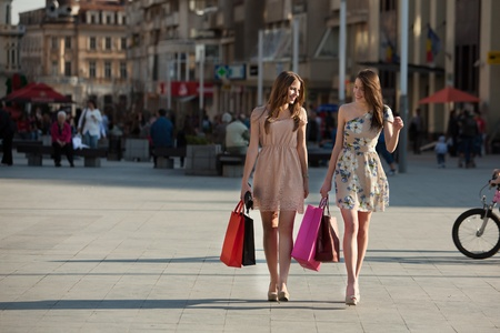 two young women with shopping bags walking in the city Reklamní fotografie - 13225312