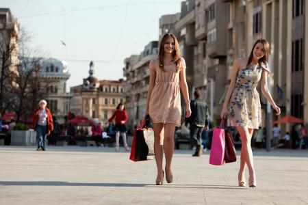 chicas comprando: dos mujeres con bolsas de compras caminando en la ciudad Foto de archivo