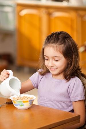 little girl having breakfast: pouring milk in the bowl photo