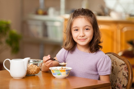 little girl having breakfast: cereals with milk photo