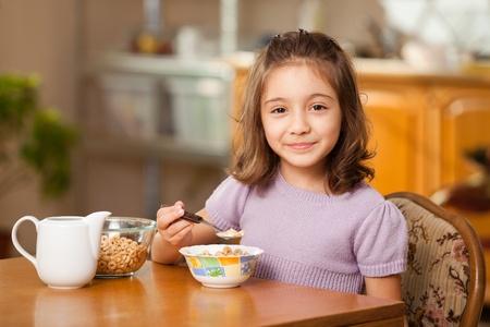 comiendo cereal: ni�a del desayuno: cereales con leche