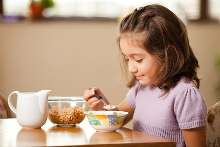 little girl having breakfast: cereals with milk