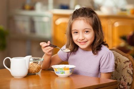 eating breakfast: little girl having breakfast: cereals with milk