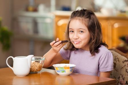 little girl having breakfast: cereals with milk photo