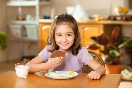 hungry children: little girl having breakfast: eating chocolate cream on a slice of bread