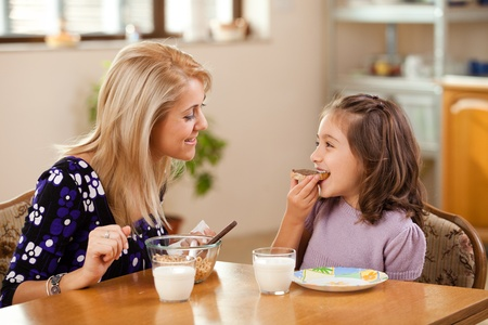 woman drinking milk: mother and daughter having breakfast: eating chocolate cream on a slice of bread