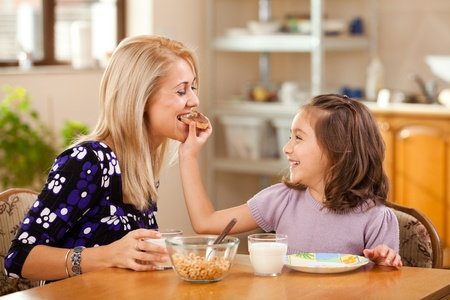 mother milk: mother and daughter having breakfast: eating chocolate cream on a slice of bread