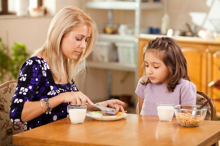 mother and daughter having breakfast: spreading chocolate cream on a slice of bread photo