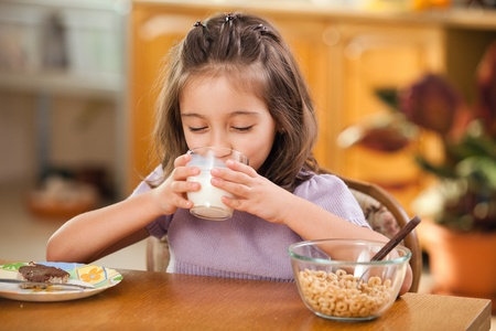 little girl having breakfast: drinking a glass of milk 免版税图像