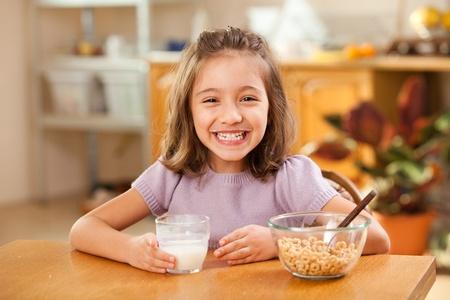 little girl having breakfast: milk moustache photo