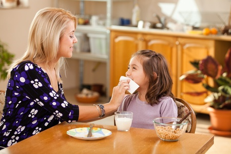 mother and daughter having breakfast: milk and cereals Stock Photo - 13256312