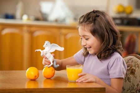 caballo bebe: niña jugando con su jugo de naranja juguete Foto de archivo