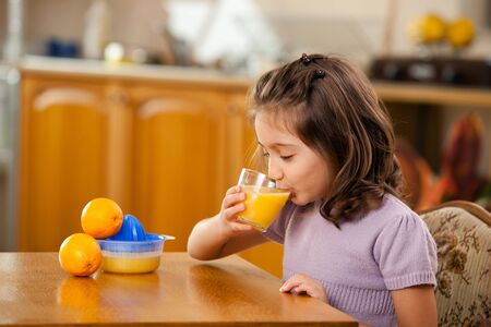 little girl drinking orange juice in the kitchen photo