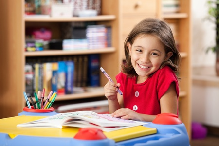 hand school education: little girl drawing on her book and having fun at playtable
