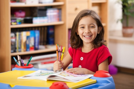home school: little girl laughing, showing her colorful pencils at her playtable Stock Photo