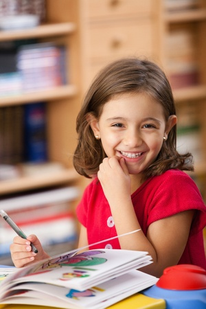 little girl smiling: little girl drawing on her book and having fun at playtable
