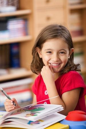jolie petite fille: petite fille en s'appuyant sur son livre et avoir du plaisir à regarderTable
