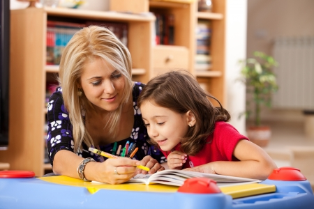 six girls: little girl and her mother drawing on a book at playtable
