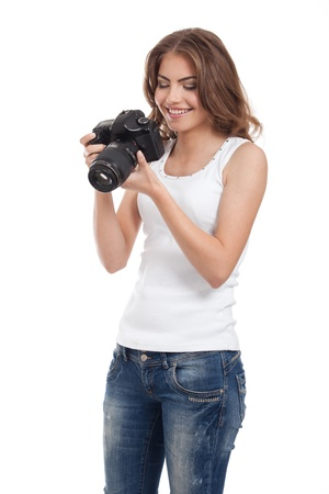 portrait of a beautiful, young woman, looking at her photo camera, isolated on white background photo