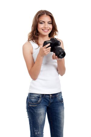 portrait of a happy, beautiful, young woman, smiling,  holding a photo camera, isolated on white background photo