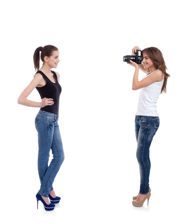two young women, photographer and model, shooting, on white background photo