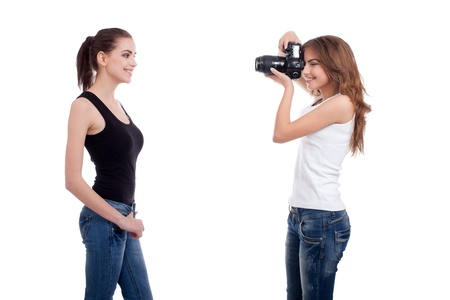 two young women, photographer and model, shooting, isolated on white background photo