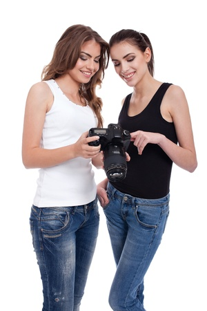 two young women, photographer and model, looking at pictures on photo camera, isolated on white background