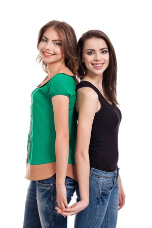 girls holding hands: two teenage girls holding hands, smiling, isolated on white background Stock Photo