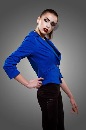 blue grey coat: fashion shot of young woman with creative make-up, blue coat, on grey background