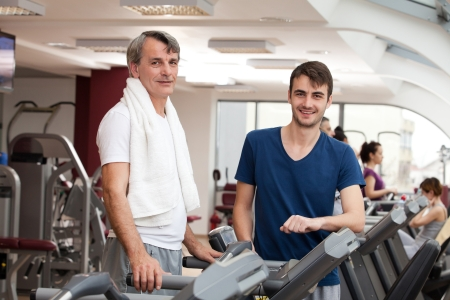 young man smiling and his father training in the gym: treadmill Stock Photo