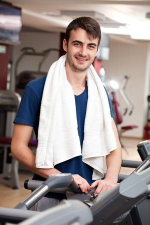 young man training in the gym, smiling, with towel around his neck photo