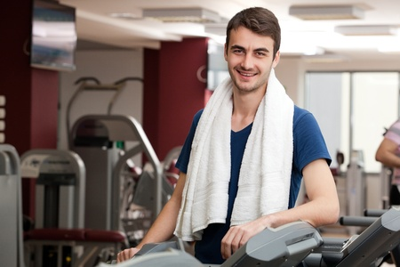 young man training in the gym, smiling, with towel around his neck Reklamní fotografie