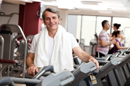 man training in the gym, smiling, with towel around his neck photo