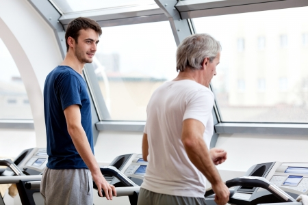 young man smiling and his father training in the gym: treadmill Reklamní fotografie