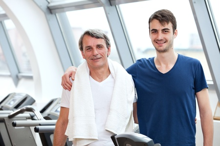 young man and his father training in the gym: treadmill, smiling photo