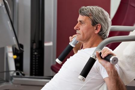 apalancamiento: hombre entrenamiento en el gimnasio, sonriendo, press de hombros apalancamiento