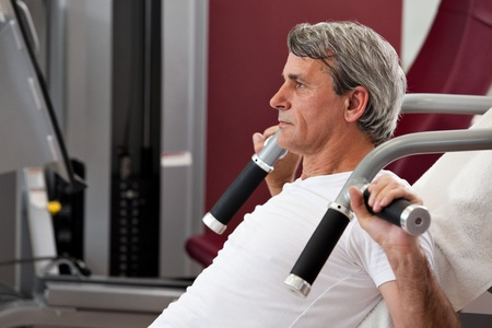 older men: man training in the gym, smiling, leverage shoulder press Stock Photo
