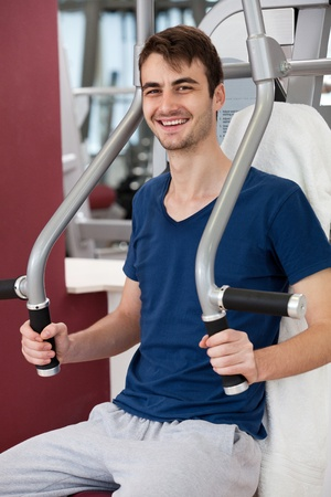leverage: young man training in the gym, smiling, leverage chest press
