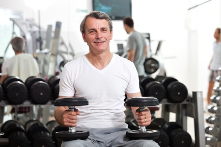man training in the gym, smiling, holding dumbbells, preparing to do biceps or shoulders photo