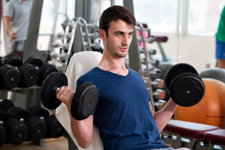 young man training in the gym: biceps - seated dumbbell curl
