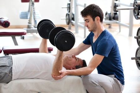 young man helping his father in the gym: chest - dumbbell bench press
