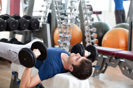 young man training in the gym: chest - dumbbell bench press 免版税图像
