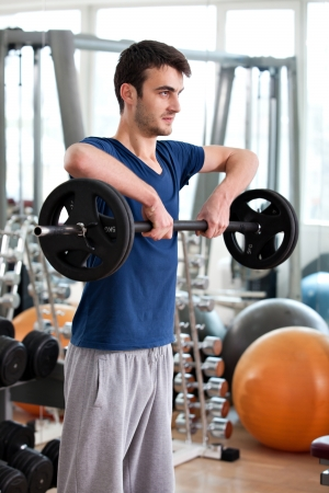 upright row: young man training in the gym: shoulders - upright barbell row