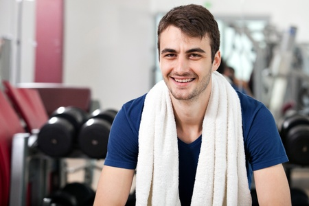 young man training in the gym, smiling, seated, with towel around his neck