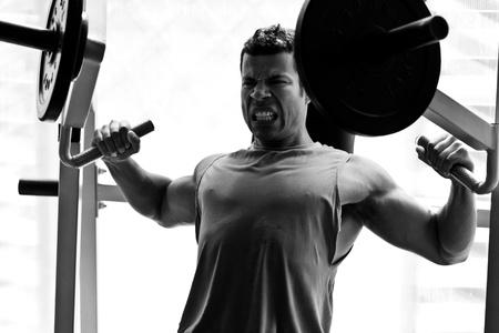 muskeltraining: k�nstlerische Schuss, Schwarz und Wei�, von einem jungen Bodybuilder hartes Training in der Turnhalle Steigung Brustpresse