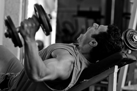 artistic shot, black and white, of a young bodybuilder hard training in the gym  incline dumbbell press photo