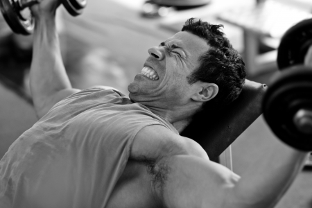 artistic shot, black and white, of a young bodybuilder hard training in the gym  incline dumbbell press Stock Photo